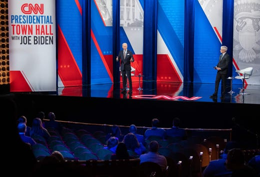 President Joe Biden, left, participates in a CNN town hall hosted by CNN anchor Anderson Cooper at the Pabst Theater in Milwaukee, Wisconsin, Feb. 16, 2021.