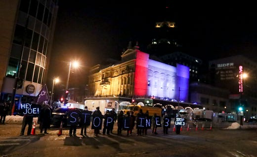 Protesters line up with a sign displaying 'Hey Joe! Stop Line 3' before President Biden speaks inside of the Pabst Theater for a town hall with CNN in Milwaukee.