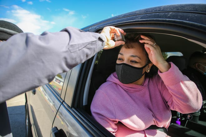 Deacon John Eric Munson administers ashes by sprinkling a salt shaker of ash in place of smudging a cross on Norma Amador's forehead in a touch-free drive thru for Ash Wednesday at Our Lady of Health Catholic Church in Las Cruces on Wednesday, Feb. 17, 2021.