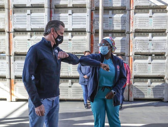 California Governor Gavin Newsom greets registerd nurse Arlene Arrechea before holding a press conference in Coachella, Ca., February 17, 2021.