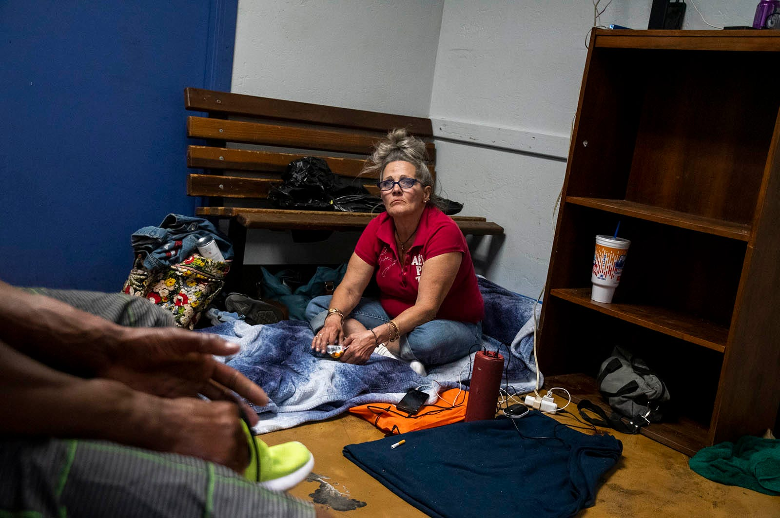 Darlene Carchedi speaks with friend Romeo Lopez as they charge their phones inside the Andre House on Feb. 27, 2020, in Phoenix.