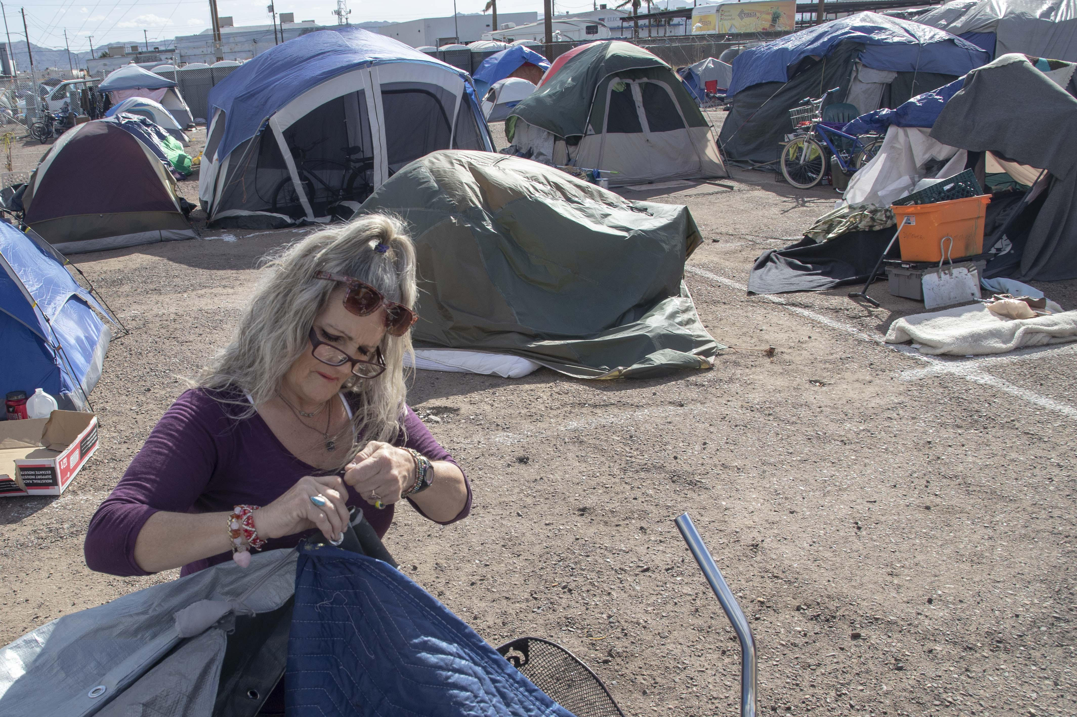 Darlene Carchedi works on a tent in an encampment in downtown Phoenix on Feb. 16, 2021. Darlene lost her previous tent and many of her belongings in a fire in December 2020.