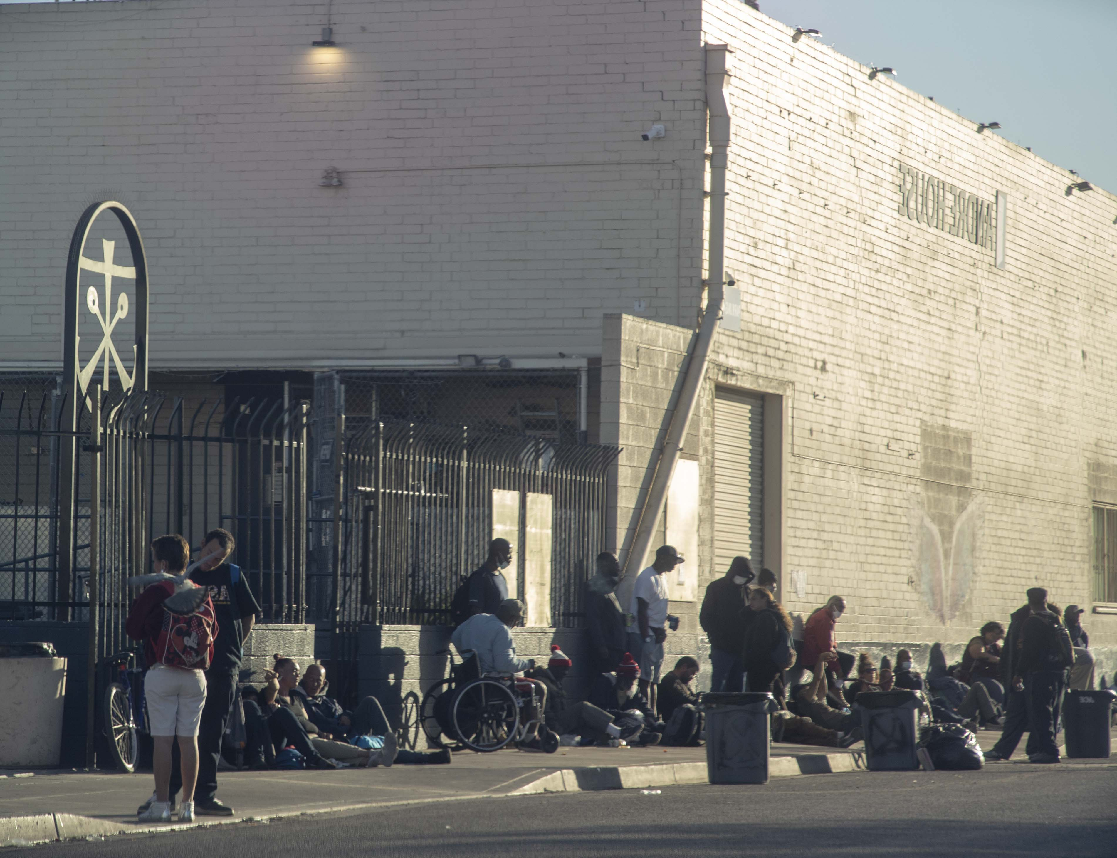 People experiencing homelessness hang out outside the Andre House on Feb. 16, 2021.