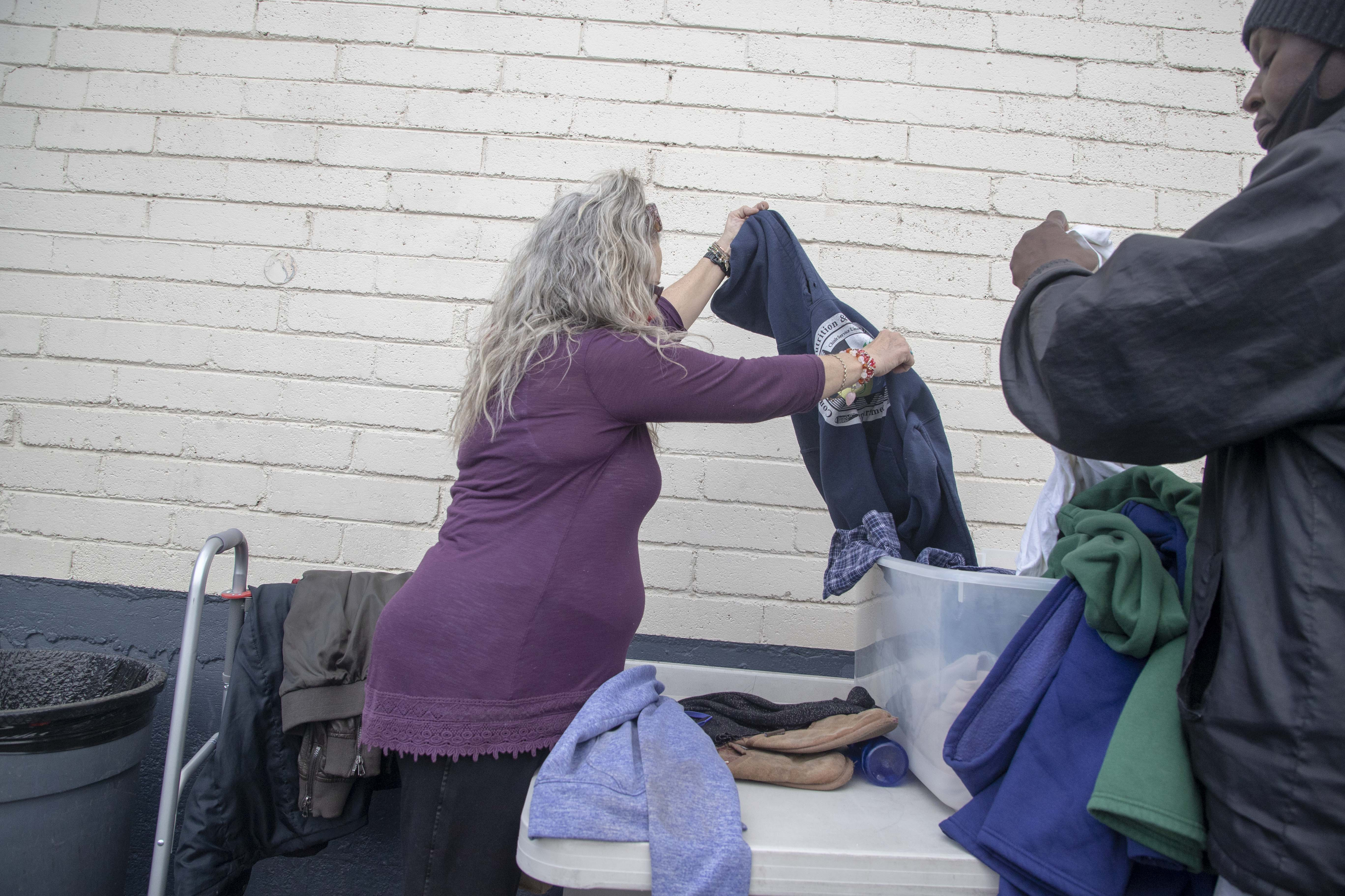 Darlene Carchedi sorts through donated clothes on Feb. 16, 2021, for herself and other homeless women at Andre House in Phoenix. She says she worries about who would do the job if she were to find permanent housing.