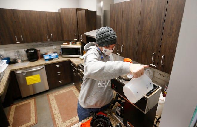 Eden Village resident Mirenda Barrows makes coffee as she volunteers in the emergency shelter set up at Eden Village on Tuesday, Feb. 16, 2021.