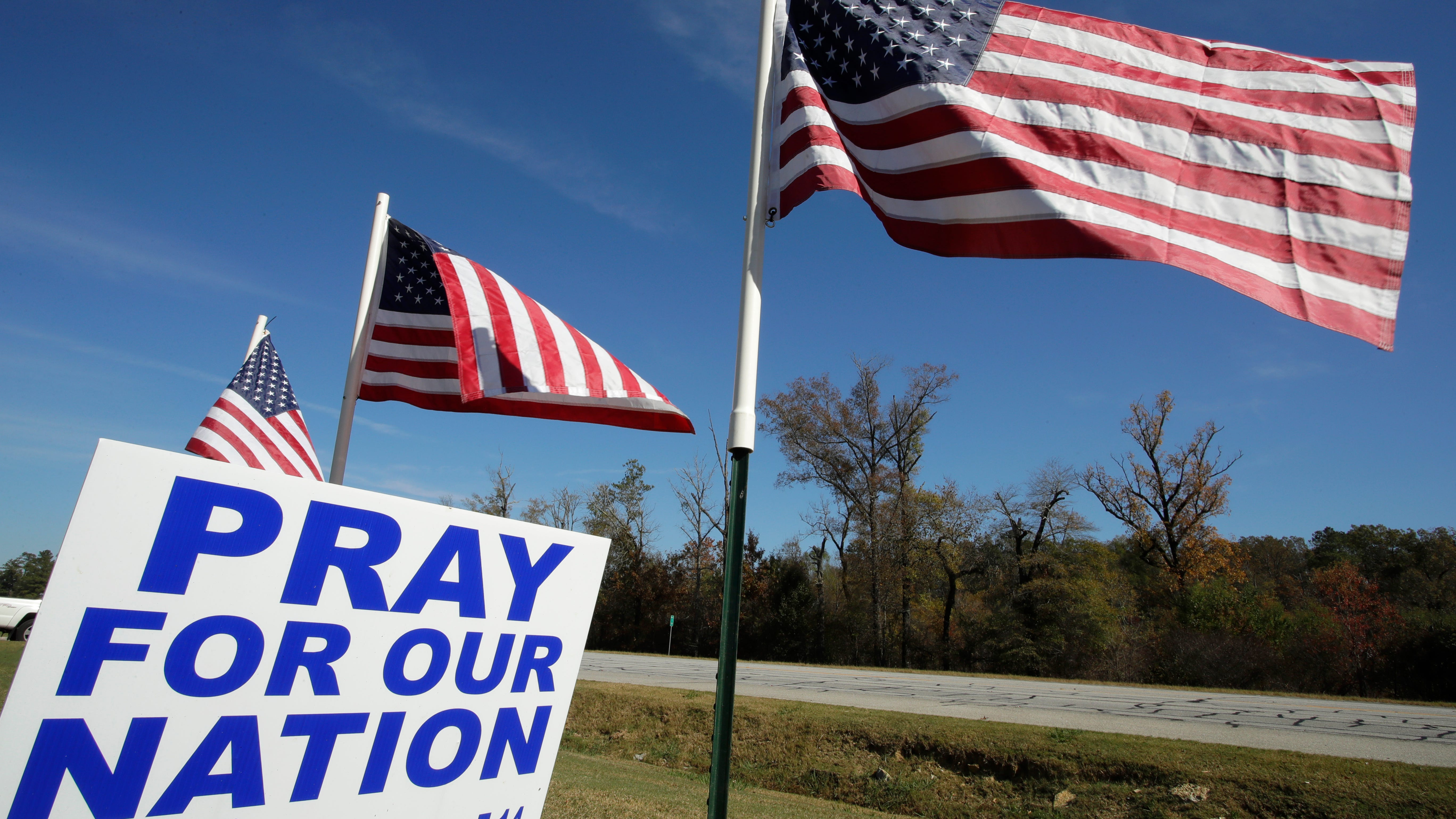 American flags fly over a sign reading 'Pray For Our Nation' on Highway 27 Friday, Nov. 6, 2020, in Rome, Ga. (AP Photo/Ben Margot)