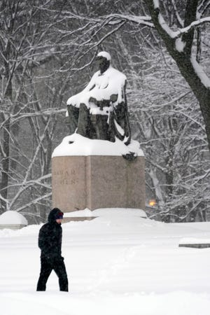 A lone man walks in a light snow storm through Chicago's Grant Park Sunday, Jan. 31, 2021, past a snow covered statue of Abraham Lincoln.