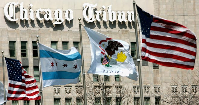 FILE - In this April 12, 2006, file photo, flags wave near the Chicago Tribune Tower in downtown Chicago. Newspaper publisher Tribune has agreed to be sold to Alden Global Capital, a hedge fund known for cutting costs and eliminating newsroom jobs, in a deal valued at $630 billion.