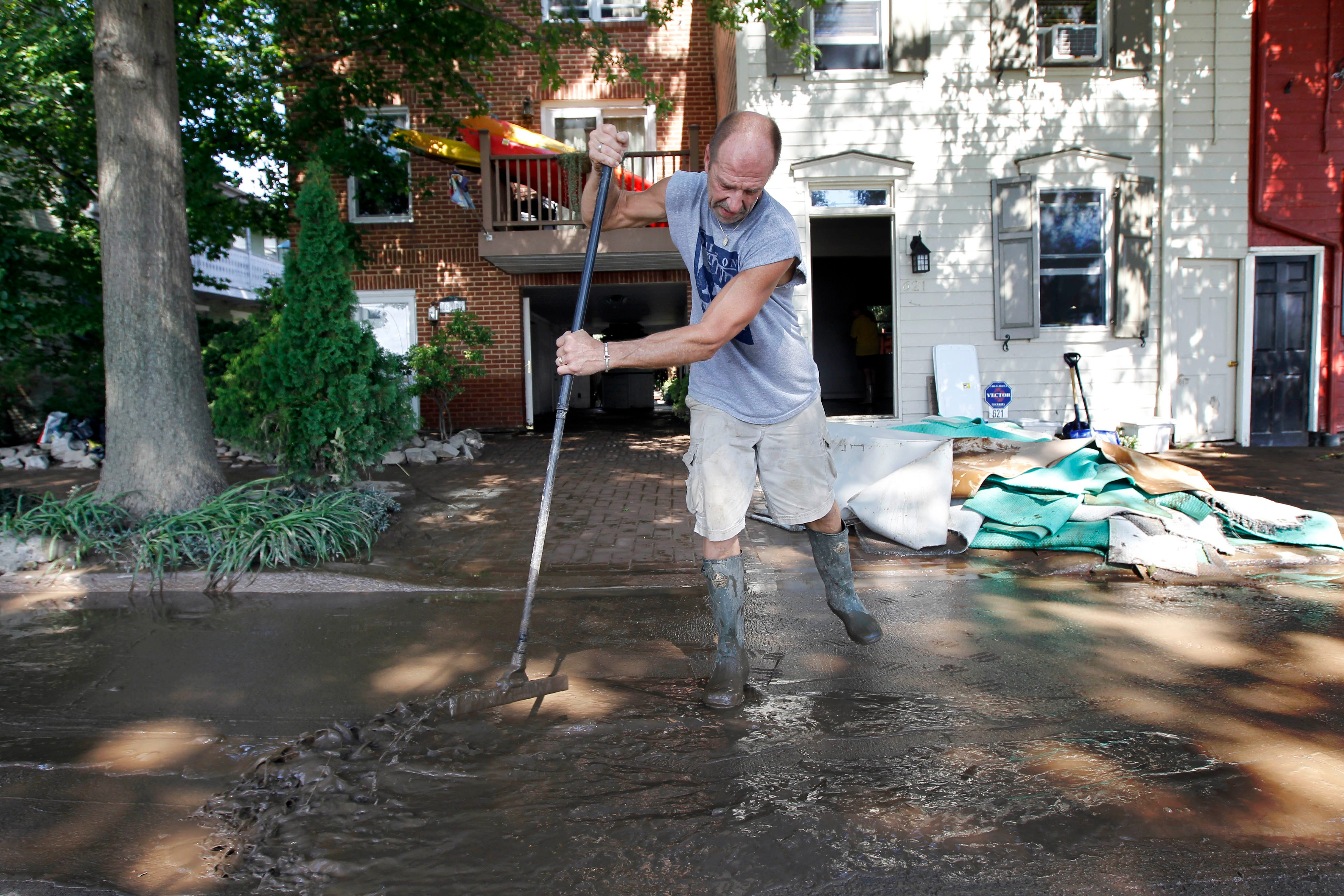 Michael Snyder scrapes away the mud after flooding from the Susquehanna River caused by the remnants of Tropical Storm Lee, Saturday, Sept. 10, 2011 in the Shipoke area of Harrisburg, Pa.