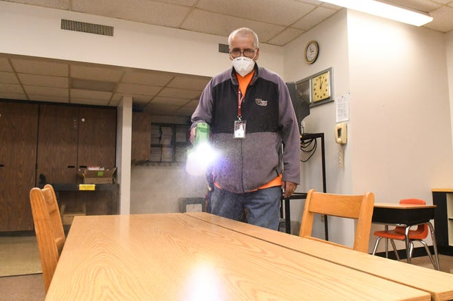 Custodian Rick Wilson cleans a desk using an electrostatic sprayer on Tuesday at John S. Clarke Elementary School in Pottsville, Pa., amid preparations for students' return to in-person classes.