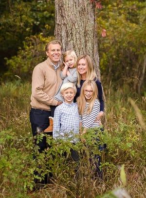 Abbie Adair Reinhard, husband Josh, and their three children pose for a summer 2020 family photo.