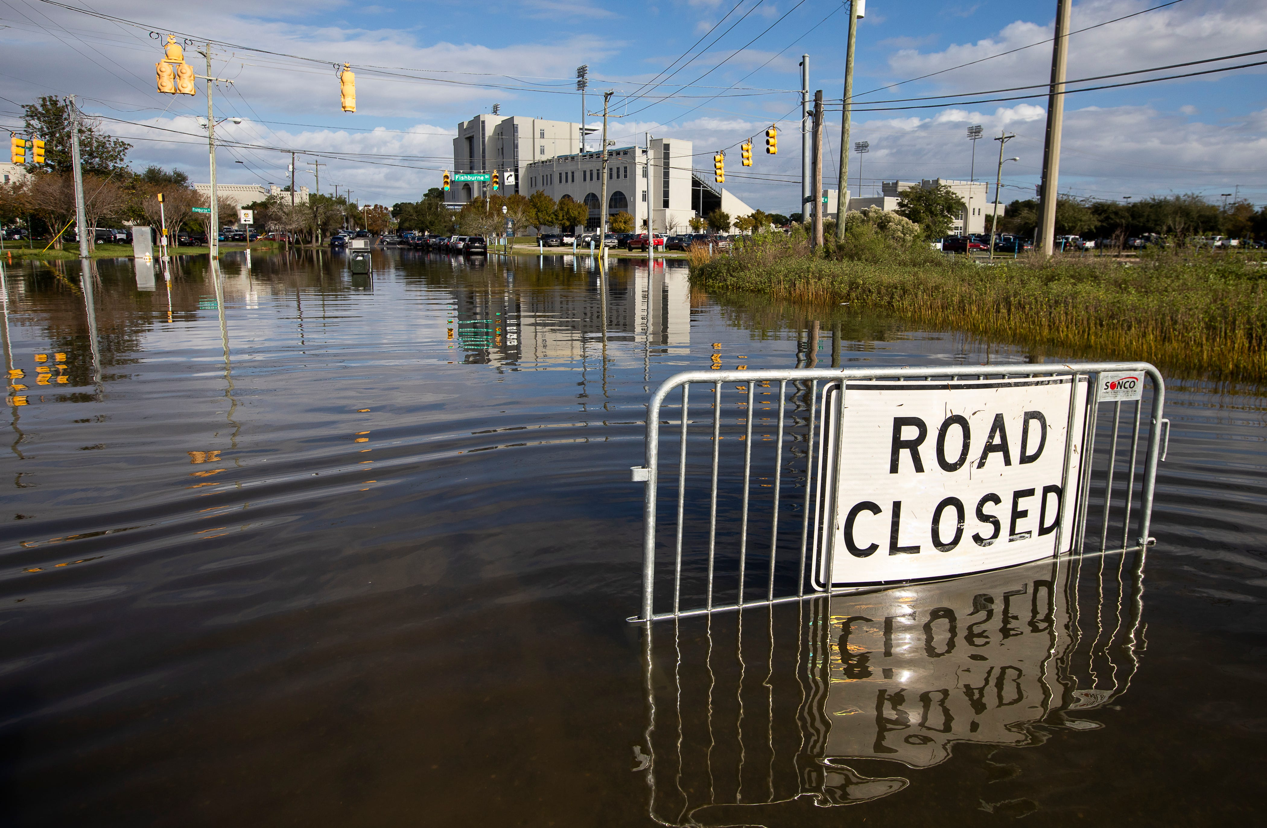 A road closed sign tells motorists to not pass through the floodwaters at a Charleston, S.C., intersection as a king tide rolls in. South Carolina is home to some of the biggest gaps in current flood insurance premiums vs. actual risk.