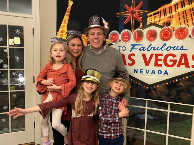 Abby Adair Reinhard, her husband Josh, and their three kids pose for a family photo during a celebration at home where they pretended to travel to Las Vegas.