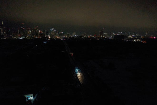 Vehicles drive down East 7th Street as power outages darken most of East Austin on Feb. 17. [AMERICAN-STATESMAN/FILE]