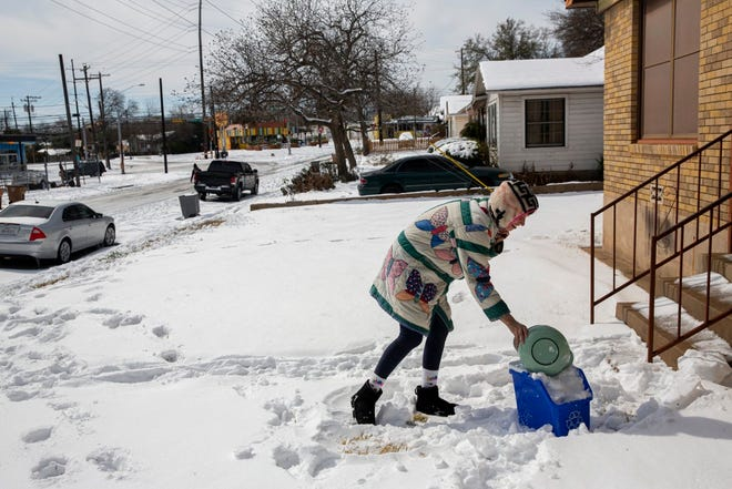 Rebecca Wright fills a recycling bin full of snow to boil into drinking water at her home in Austin on Tuesday, Feb. 16, 2021. Wright has been without water for nearly 24 hours when a pipe burst.
