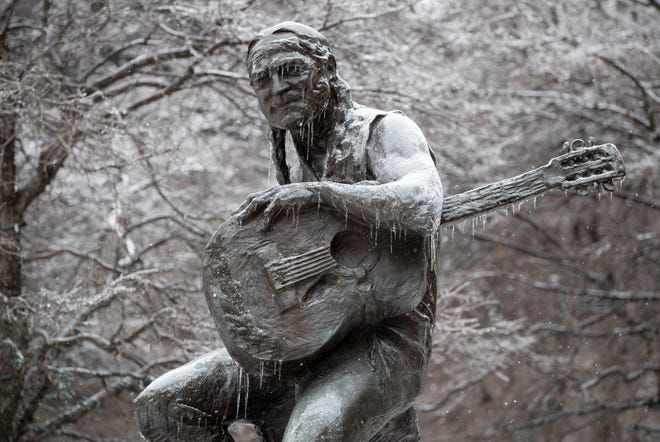 The statue of Willie Nelson in downtown Austin is covered with ice as snow begins to fall again on Thursday.