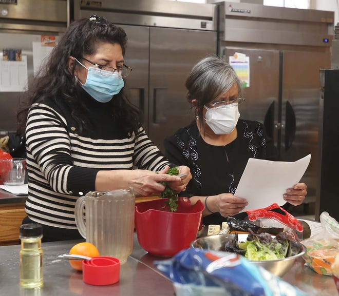 Nancy Auquilla, left, and Rita Aggarwal of Proyecto RAICES lead a healthy cooking session in the kitchen at St. Mary's Catholic Church in Akron.