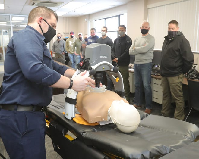 Akron Fire Department fire medic Mike Fuller demonstrates Lucas, a chest compression device, to members of the Akron Police Department on Thursday.