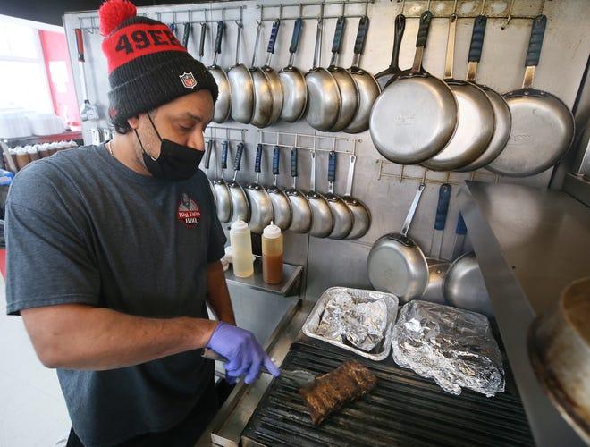 Eugene Wilson Jr., owner of Big Eu'es BBQ, makes a half rack of ribs at his restaurant in Cuyahoga Falls.
