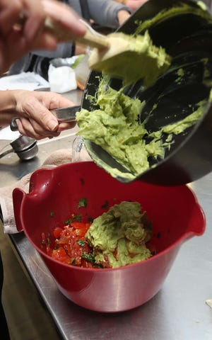 Nancy Auquilla of Proyecto RAICES spoons mashed avocados into a bowl with other ingredients to make guacamole as she leads a healthy cooking session Feb. 13 at St. Mary's Catholic Church in Akron.
