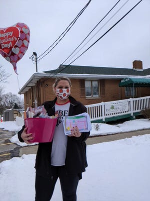 First-graders at West Branch Local Schools' Early Learning Center took part in a project to help give some cheer to residents of Bel Air Care Center in Alliance. The students in the classes of Jessica Scullion, JoAnn Ross and Martina DiNello worked to create valentines for the residents, as part of a packet that included a game book and some personal care items. Here, a staff member prepares to drop off the packets, along with a balloon that celebrated Valentine's Day.