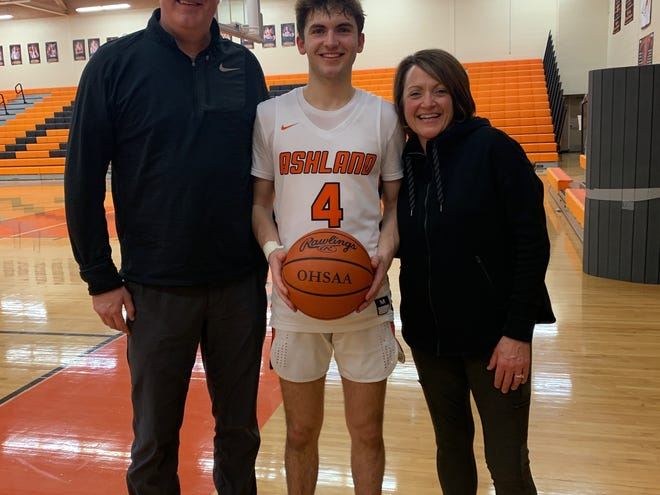 Ashland's Luke Denbow (center) poses for a picture with his parents, Dan and Susan Denbow, after scoring his 1,000th career point on Feb. 13.