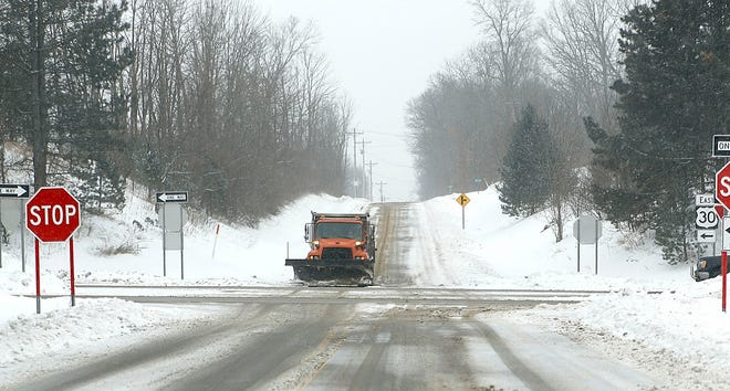 An Ashland County snow plow is seen waiting to cross U.S. Route 30 from the south on County Road 1095 as the area got another coating of snow on Thursday. While the snow is expected to taper off by the weekend, the temperatures are predicted to drop. The low temperature Saturday could be as low as 3 degrees with highs in the low 20s. Sunday will start warming up to highs in the low 30s and lows in the high 20s, which is the forecast for Monday, too.