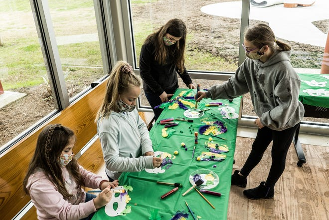 From left, Elise Marcel, Hannah Hessel, Morgan Marcel and Kaylin Hessel participate in Mardi Gras mask-making at the Houma Area Visitors Center Wednesday.