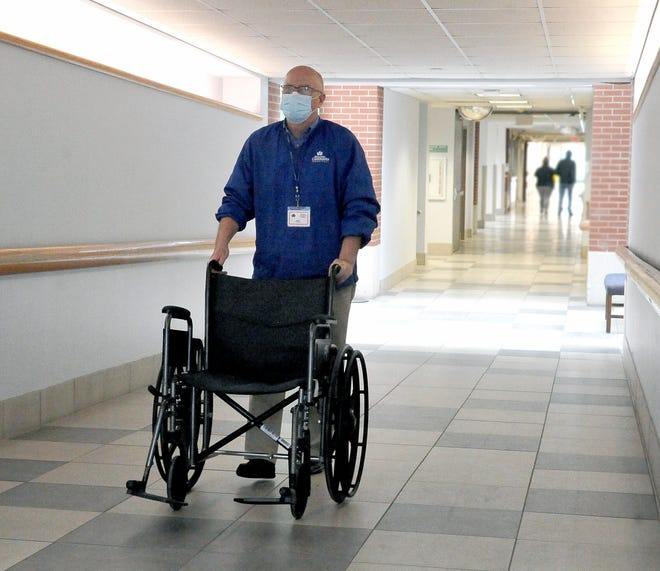 Herb Hershberger pushes a wheelchair down a hallway at the Wooster Community Hospital where he volunteers two days a week. The primary responsibility for volunteers at the hospital is to wheel patients out of the hospital and help bring those in who need a little extra help.