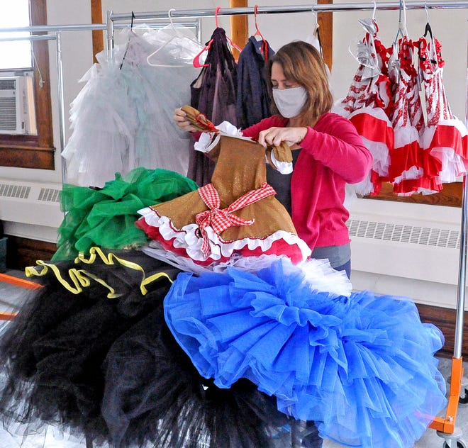 Allison Green, a parent volunteer at the Wayne Center for the Arts, sorts through a pile of costumes for the dance program in mid-February.