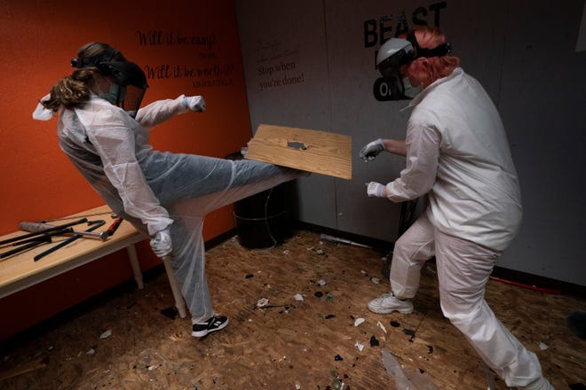 Piper Mape, 17, right, watches as her sister, Berkley, 15, kicks a wooden board in a rage room Feb. 5 during a session to help relieve stress at Smash RX LLC in Westlake Village, Calif.