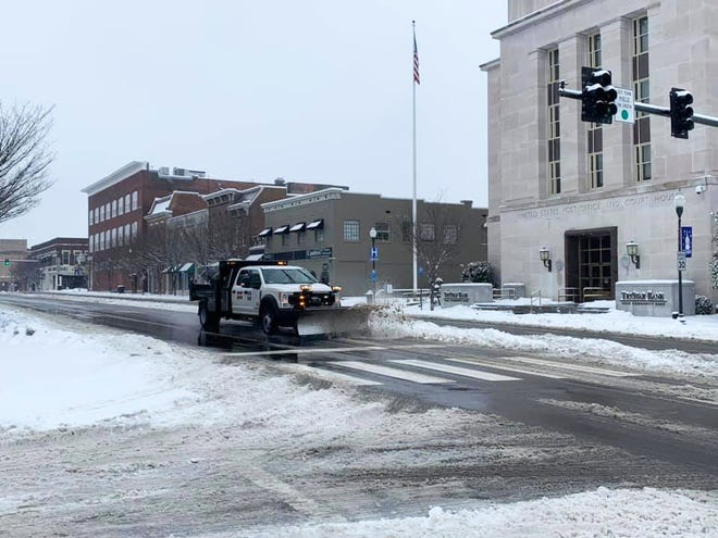 A public works truck plows snow at the intersection of Garden Street at 8th Street in Columbia, Tenn., on Thursday, Feb. 18, 2021.