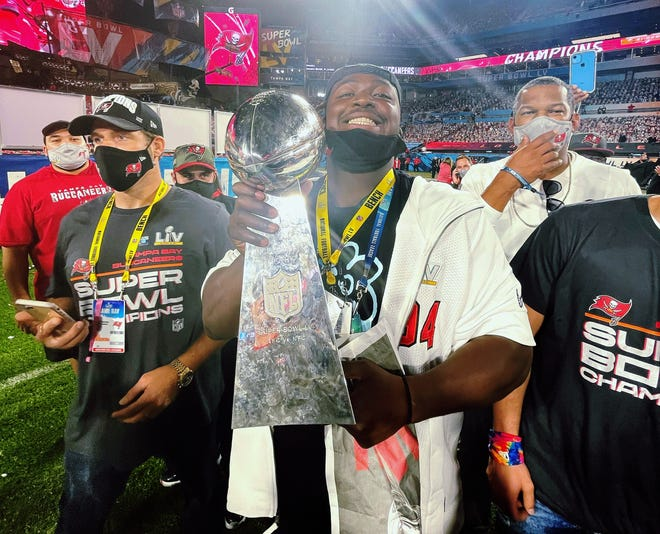 Tampa Bay Buccaneers defensive lineman Khalil Davis, center, a Blue Springs High School graduate, holds the Lombardi Trophy after the Bucs stopped his hometown Kansas City Chiefs 31-9 in Super Bowl 55.