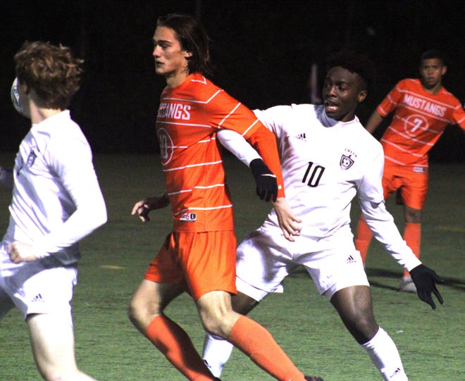 Mandarin midfielder Amar Mesic (left, in orange) challenges for possession with Spruce Creek midfielder Duzie Ejie during Wednesday's boys soccer regional.