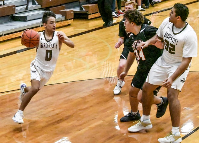 Garden City High School's Isaac Flores, left, drives the baseline for a basket against Guymon off a screen by Trey Nuzum earlier this month at GCHS. Flores was the high scorer with 15 points Wednesday as the Buffaloes defeated Dodge City on the road.