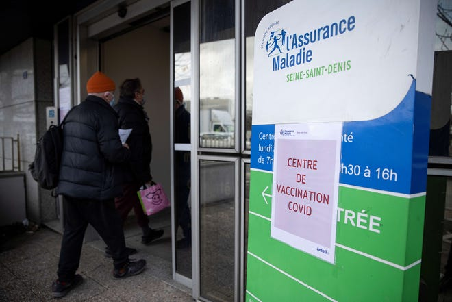 Two men arrive to be vaccinated against Covid-19, at a Covid-19 vaccination center for those deemed vulnerable or over 75 years old set up in a health center of the French Primary health insurance fund - CPAM, in Bobigny on the outskirts of Paris on Feb. 17, 2021.
