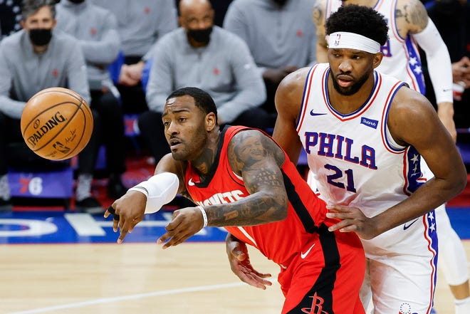 The Houston Rockets' John Wall (1) passes ahead of pressure from the Philadelphia 76ers' Joel Embiid (21) during the first quarter against at Wells Fargo Center in Philadelphia on Wednesday, Feb. 17, 2021. Despite 28 points from Wall, the Sixers posted a 118-113 as Embiid missed a triple-double by one assist.