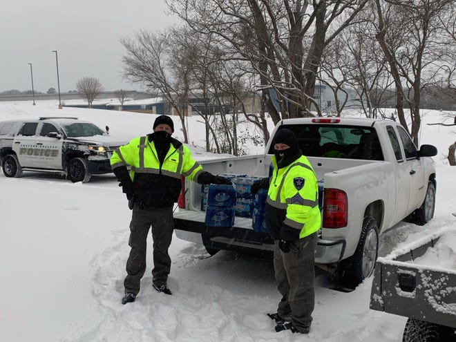 Grayson College police officers prepare to deliver water to students at the school's residence halls.