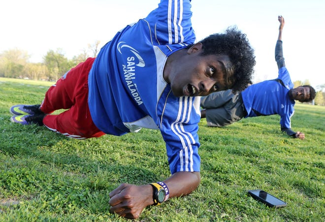 Somalians Saadiq Mohammed and Sa'ad Hussein stretch in Forest Park on April 7, 2016, in St. Louis, as they prepare to practice soccer.