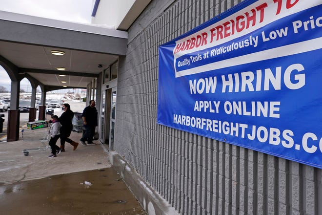 "In this Dec. 10, 2020 file photo, a ""Now Hiring"" sign hangs on the front wall of a Harbor Freight Tools store in Manchester, N.H. Employers cut back sharply on hiring in December, particularly in pandemic-hit industries such as restaurants and hotels, as soaring virus infections and government restrictions weakened the economy that month."