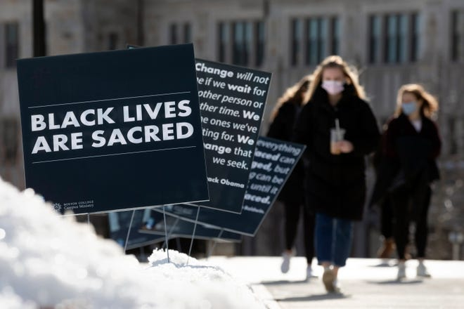 Students walk past Black History Month posters on the Boston College campus, Feb. 17, 2021, in Boston. Harassment by white male students targeting Black and Latina women housed in a Boston College dormitory has revived concerns about racism on campus.