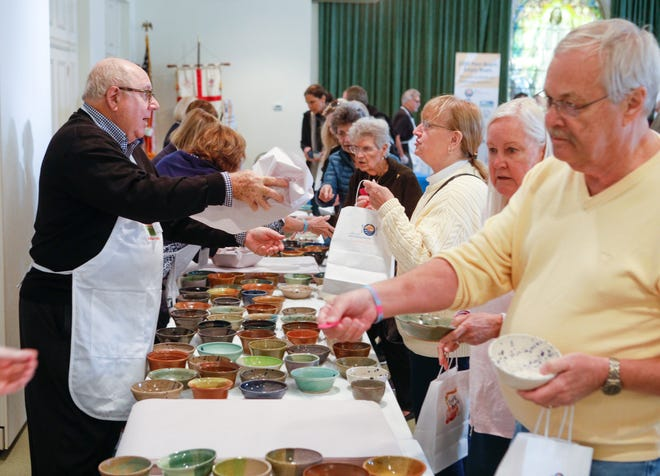 Empty Bowls attendees select a complimentary gift bowl crafted by Outlaw Pottery during the February 2020 event at the Episcopal Church of Bethesda-by-the-Sea. This year's Empty Bowls will be a drive-thru pick-up event because of the coronavirus pandemic. [DAMON HIGGINS/palmbeachdailynews.com]
