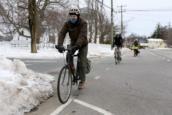 Matthew Glenn, Jonathan Sandberg and Annie Poubeau, members of the Seacoast Area Bicycle Riders, ride down the Middle Street bike lane Thursday, Feb. 18, 2021, in Portsmouth.