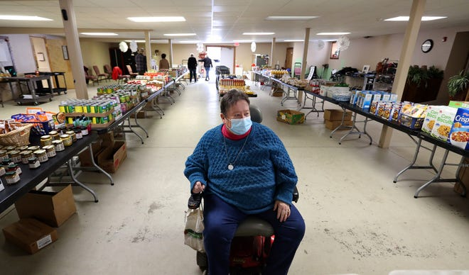 """Betty Eaton of We Care Food Pantry shows the rows of food being set up Thursday, Feb. 18, 2021 at Restoration Church for the weekly """"shopping"""" by clients on Fridays."""
