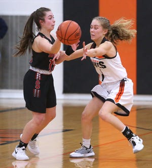 Jenna McClish (left) of Salem passes while being guarded by Maria Warner (1) of Marlington during their game at Marlington on Wednesday, Feb. 17, 2021.