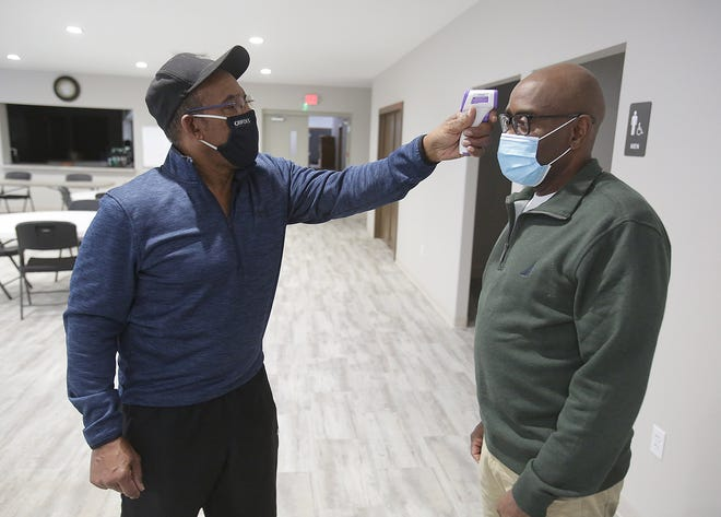 Ronald Glenn, janitor and member at Union Baptist Church in Canton, takes the temperature of Rev. Sherman Martin Jr. at the church showing just some of the measures they are taking against COVID-19.