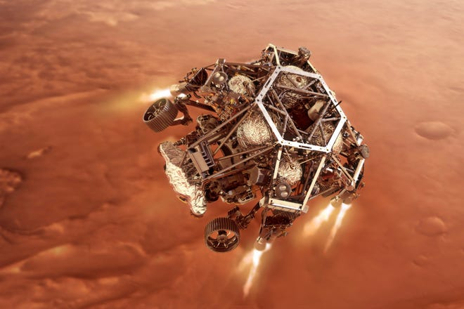 """In this illustration provided by NASA, the Perseverance rover fires up its descent stage engines as it nears the Martian surface.. This phase of its entry, descent and landing sequence, or EDL, is known as """"powered descent."""" The rover landed on Mars on Feb. 18."""
