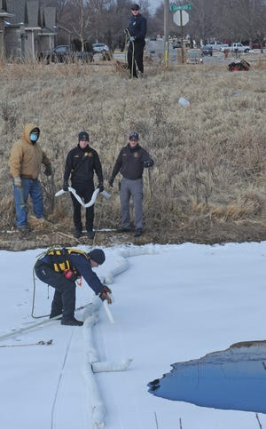 Salina first responders work together to lay oil soakers around the oil spill on the frozen pond at the Salina Municipal Golf Course on Wednesday afternoon.