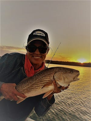Jean Parry with a beautiful sunset redfish caught with husband Don, just southeast of the Bridge of Lions.
