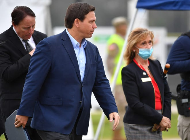 Gov. Ron DeSantis walks toward a podium, accompanied by Manatee County Commissioner Vanessa Baugh, for a press conference at a COVID-19 vaccine pop-up clinic in Lakewood Ranch. The clinic is now the subject of a federal complaint.